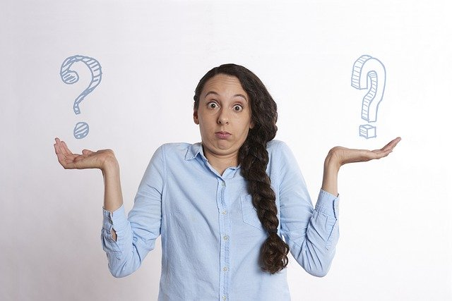 Woman shrugging with two question marks over her hands