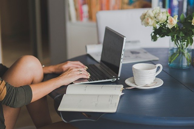 Woman with exposed, bent leg writing on laptop with coffee cup and notepad