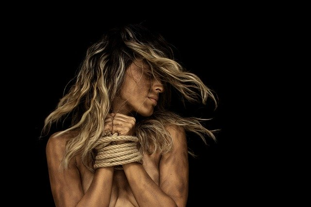 Nude woman with bound hands in front of her chest, whipping her hair